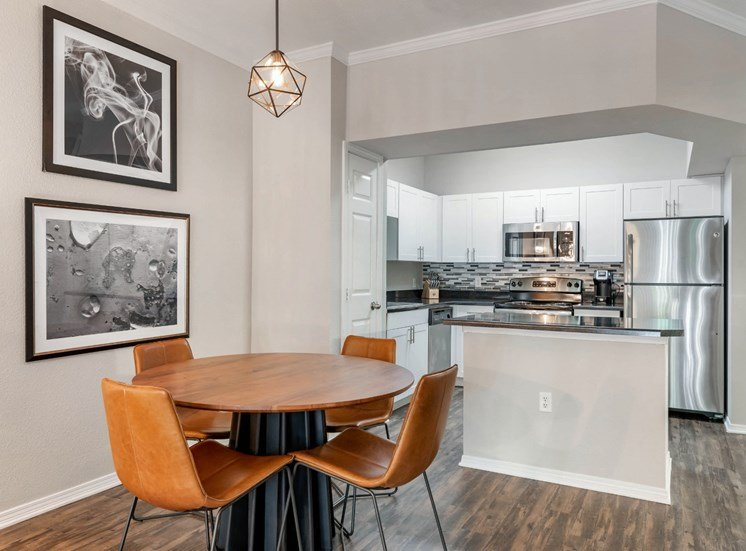 Furnished Model With Contemporary Dining Table and Art In Dining Room Next to Kitchen with Island White Cabinets and Stainless Steel Appliances