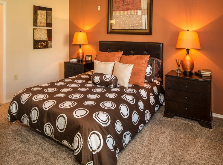 Model Bedroom with Orange Accent Wall Brown Bedding and Wood Nightstands