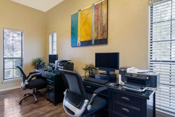 Resident Business Center with Art Mounted Between Two Windows and Two Black Desk with Computers Printers and Rolling Chairs