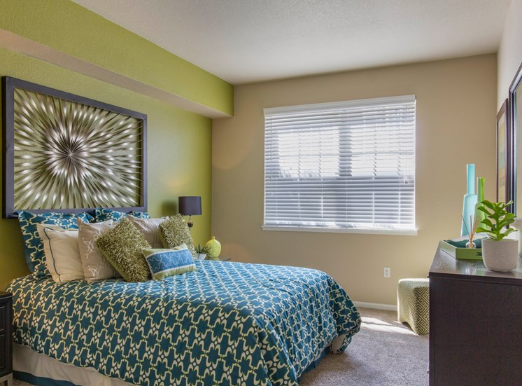 Model Bedroom with Green Accent Wall with Art Bed and Dresser