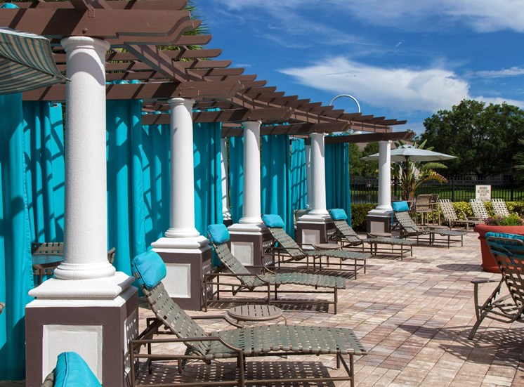 Poolside Pergola with Blue Curtains and Lounge Chairs