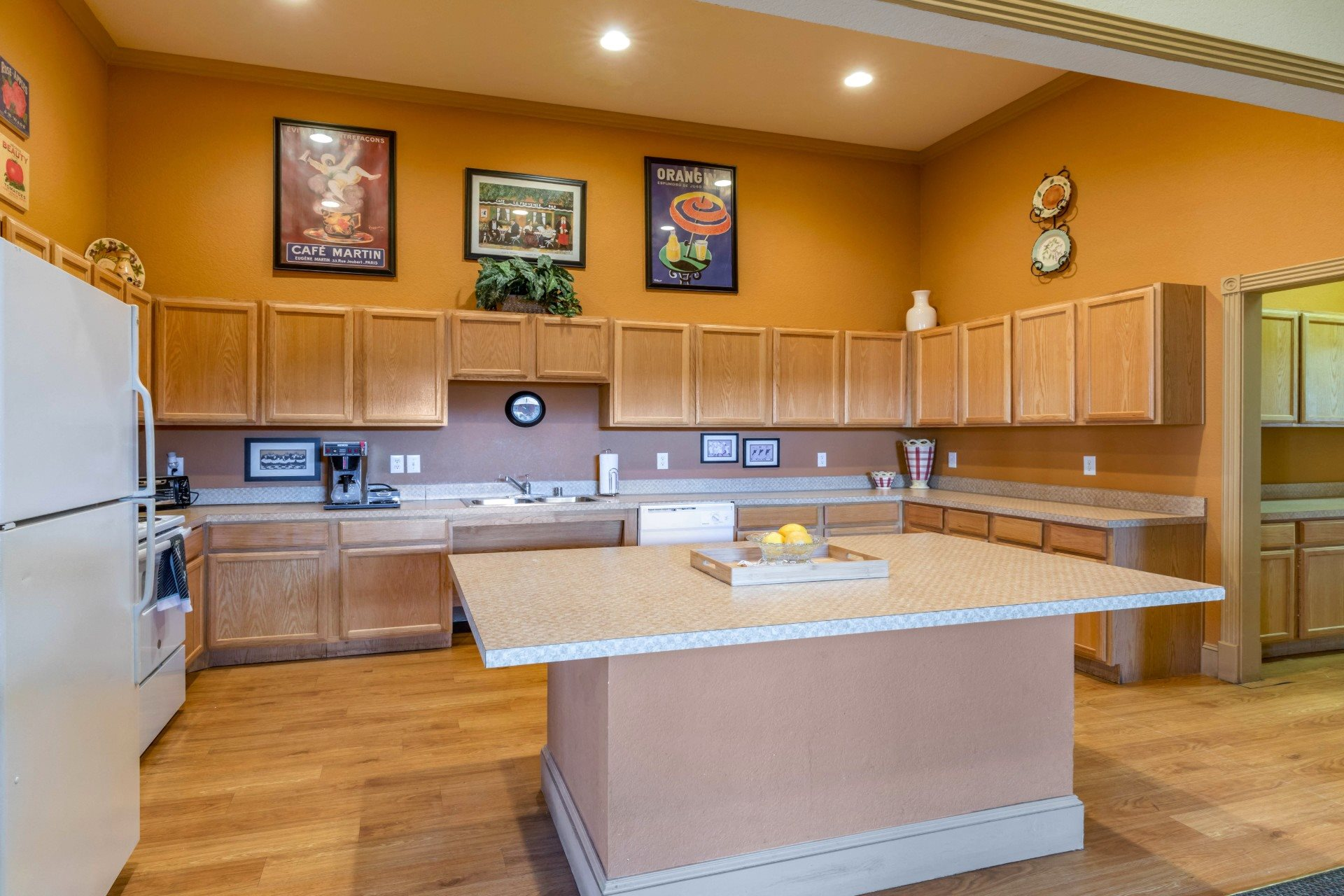 Clubhouse Kitchen with Blonde Cabinet White Counters and Large ISland