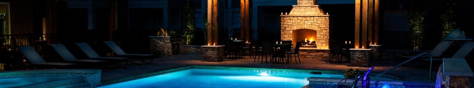 Swimming Pool Lit Up at Night with Fireplace Under Pergola and Lounge Chairs