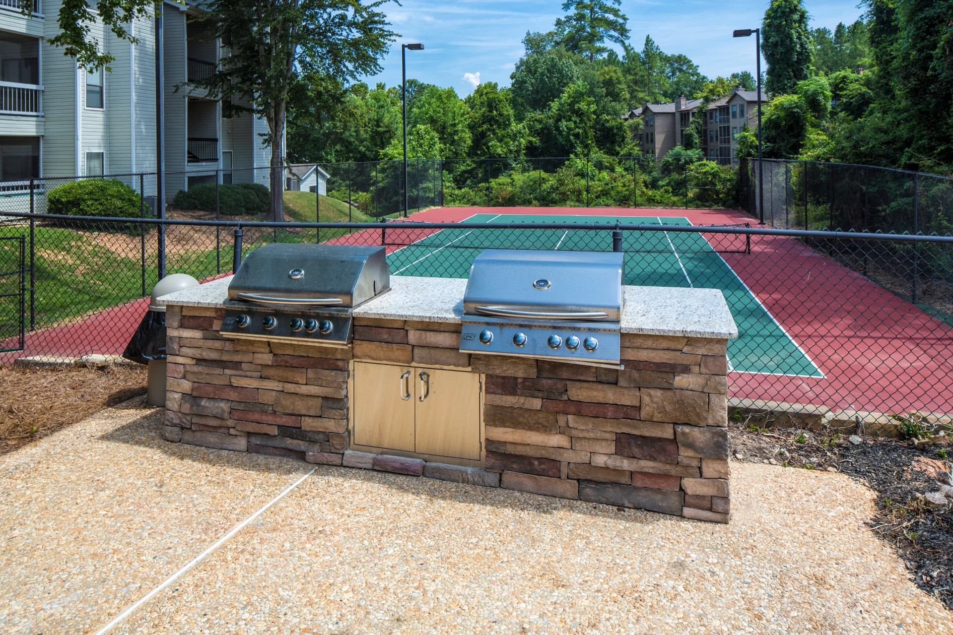 Outdoor Kitchen Next to Fenced Tennis Court with Building Exteriors and Trees in the Background