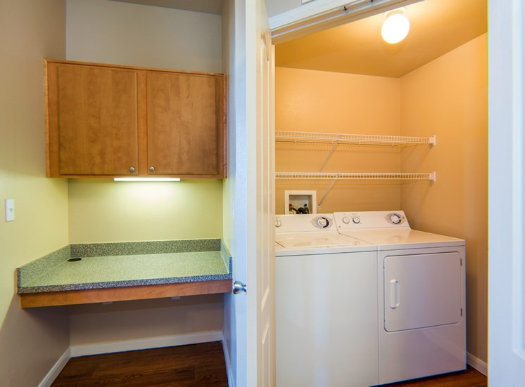 Built in Desk With Overhead Wood Cabinets Next to Laundry Closet with Full Sized Washer and Dryer Under Wired Shelves