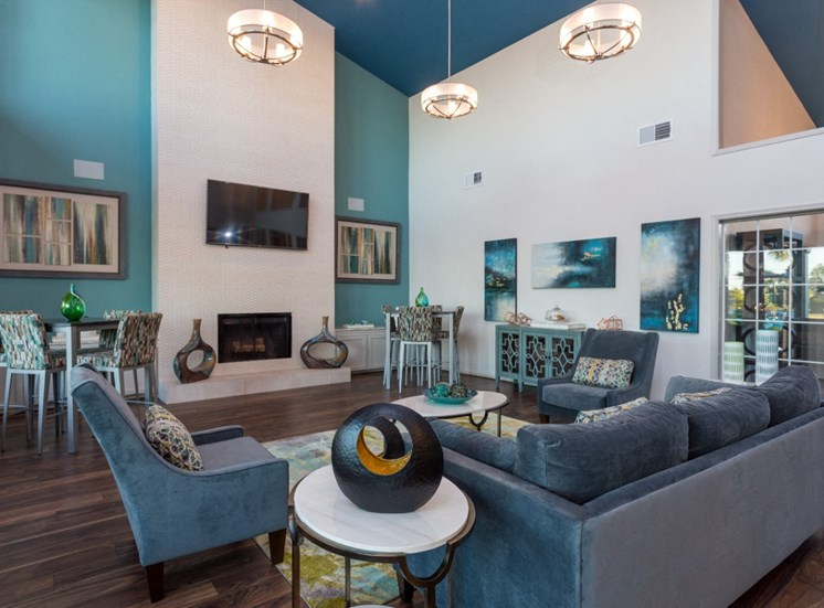 Clubhouse Seating Area with Blue and Grey Color Scheme with Couch 2 Armchairs  2 Bar Height Tables with Chairs on Either Side of Fireplace with TV Mounted