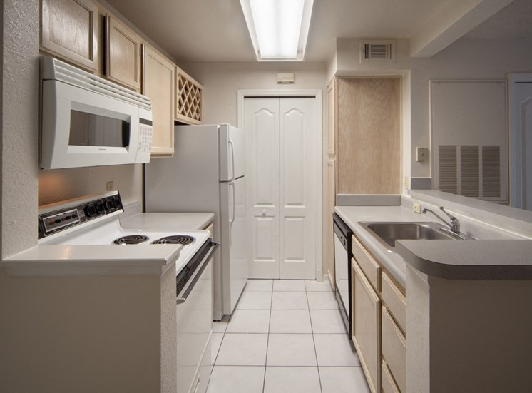 Kitchen with white appliances, double basin sink, and tile flooring