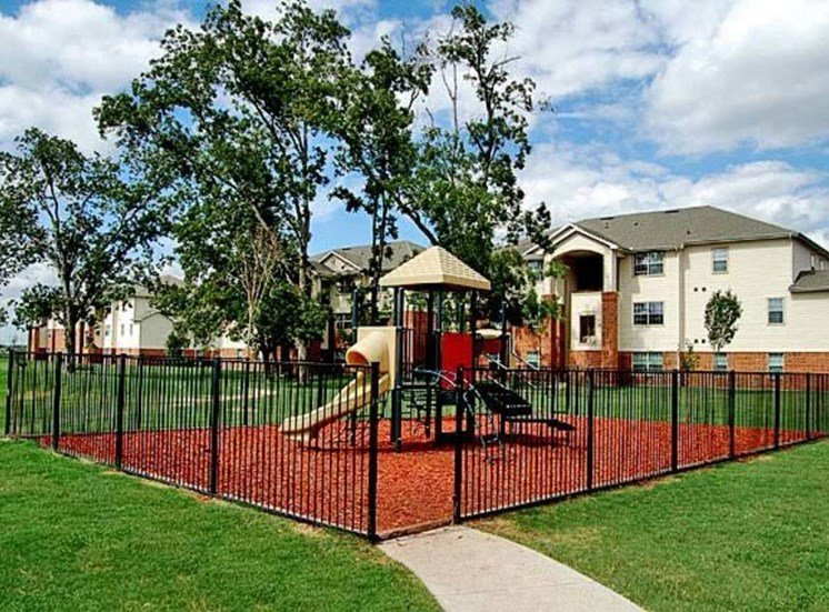 Outdoor fenced in playground with green grass surrounding it