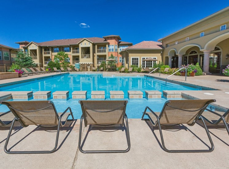 Swimming pool view with lounge chairs and tanning deck, potted flowers are also around the perimeter of the pool