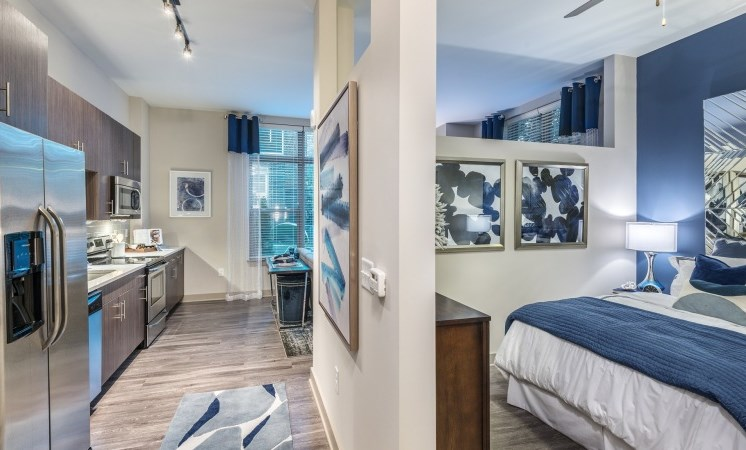Model Furnished Studio Apartment Entryway Showing Bedroom and Kitchen