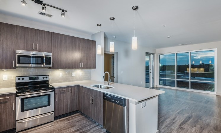 Kitchen with Open Layout and Breakfast Bar Wood Grain Cabinets and Stainless Steel Appliances and Living Room with Large Windows