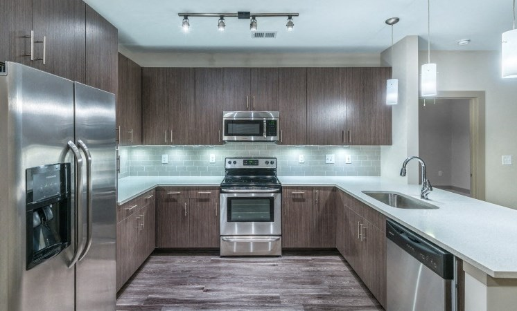 Kitchen with Open Layout and Breakfast Bar Wood Grain Cabinets and Stainless Steel Appliances