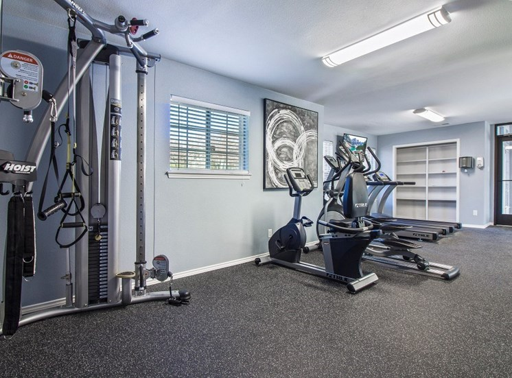 Fitness center with exercise equipment facing the wall with wall art.