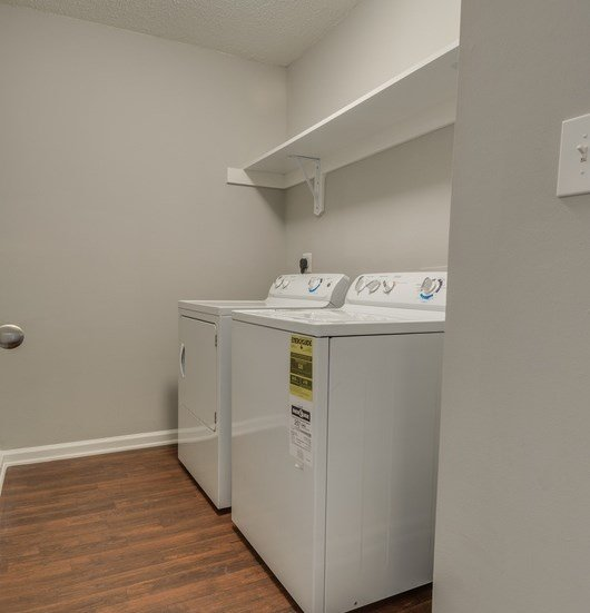 Laundry room with white washer and dryer on wood style floor