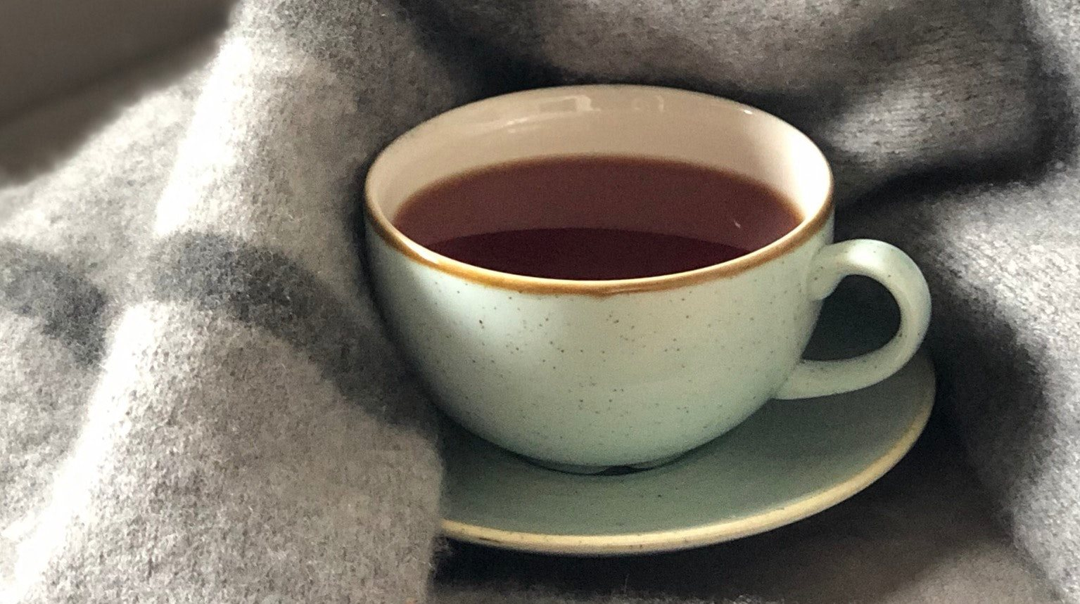 Stock Image of Tea Cup with Blanket on Grey Armchair