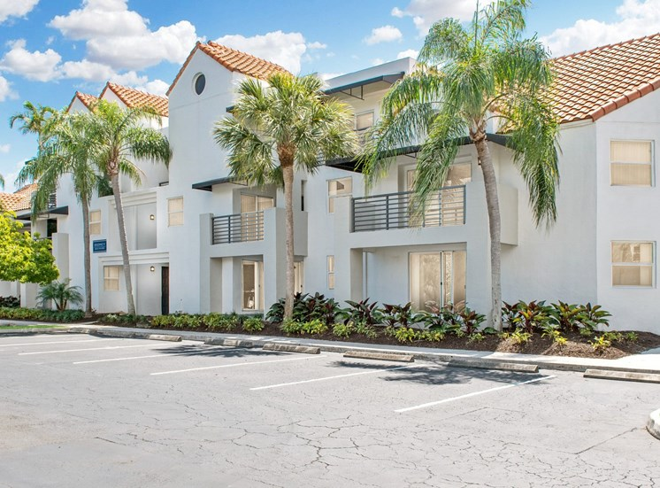 Apartment Building Exterior with Parking Lot and Palm Trees