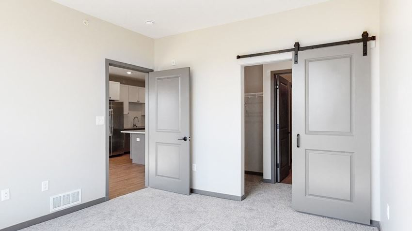 Sliding barn doors leading to closet space and the bathroom from the bedroom in the Bliss floor plan at Haven at Uptown in Lincoln, NE