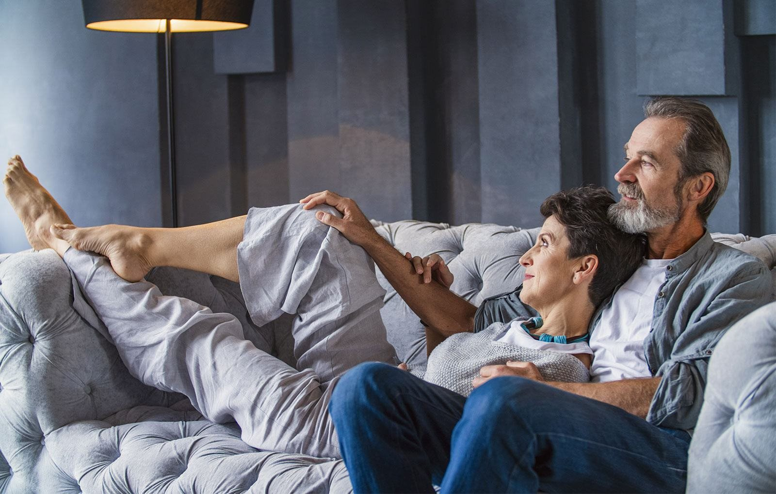 Couple relaxes on a gray couch at Haven at Uptown