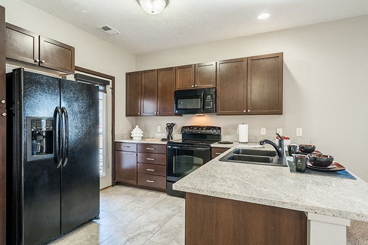 Kitchens feature dark cabinets, sleek black appliances, and gorgeous granite counter tops.