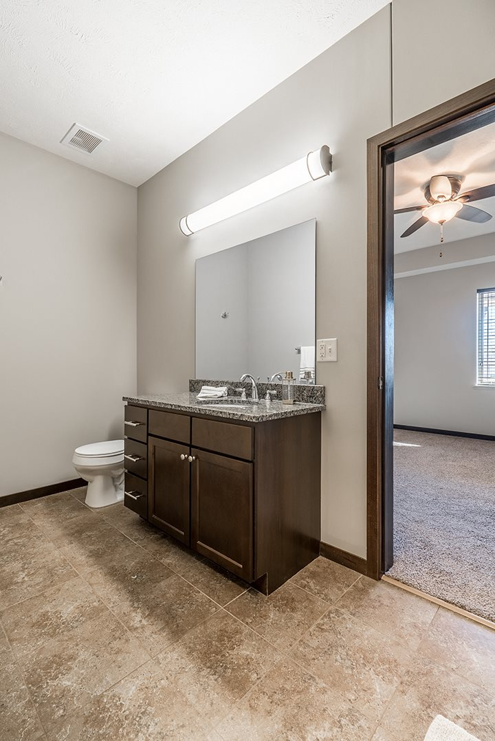 Bathrooms feature ample storage, large vanities with granite counter tops, and showers with glass doors.
