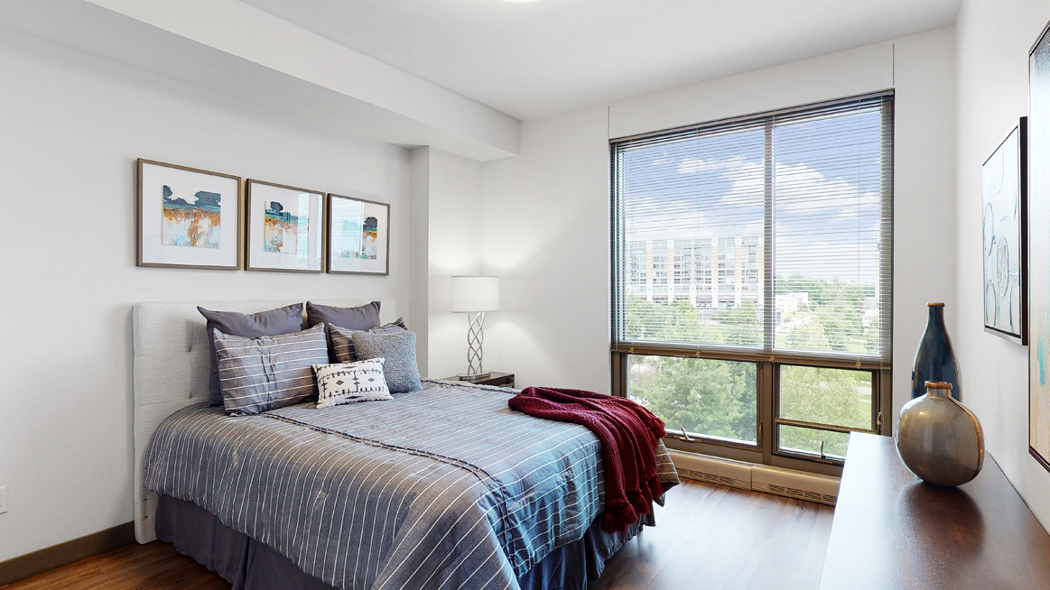 Spacious furnished bedroom with floor-to-ceiling windows a 1 bedroom floor plan Midtown Crossing Apartments Omaha