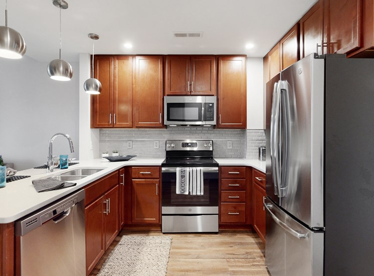 Spacious kitchen with peninsula and quartz or granite counter top and tile back splash in a 1 bedroom floor plan at Midtown Crossing Apartments Omaha