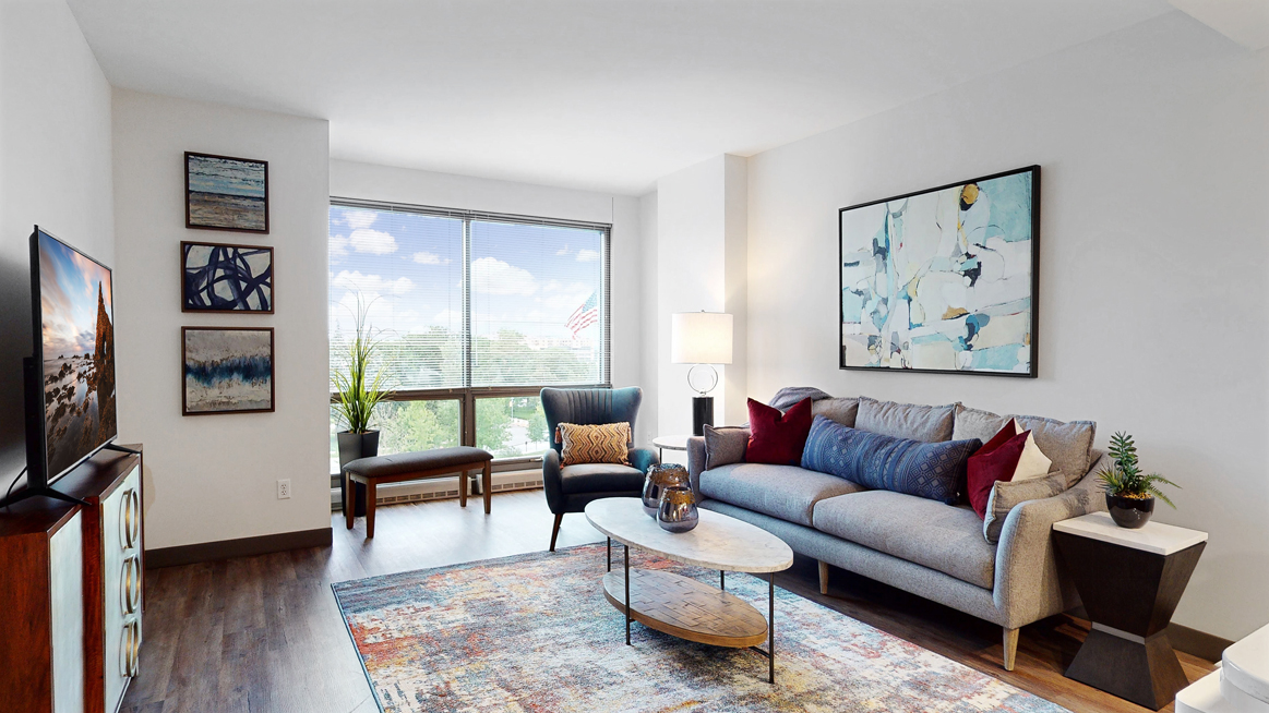 Enjoy the scenic views from the floor-to-ceiling windows in the living area of a furnished1 bedroom floor plan at Midtown Crossing Apartments Omaha