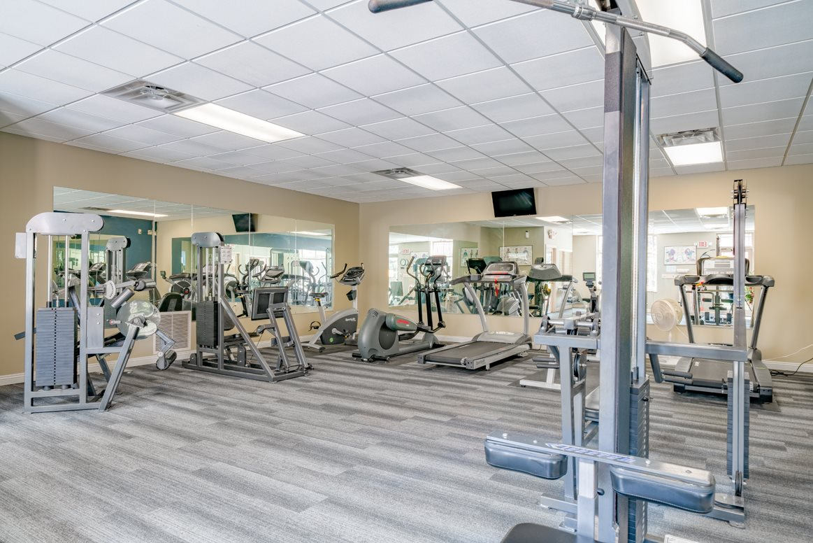 Spacious exercise room featuring cardio machines, free weights, and weightlifting machines at Southwind Villas in LaVista NE 68128