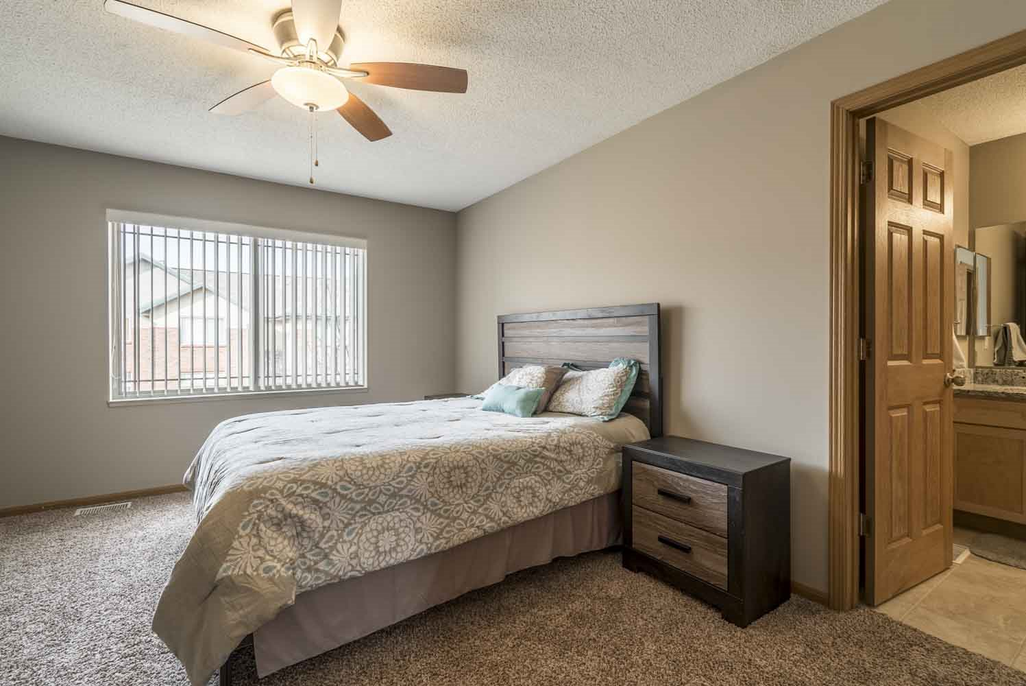 Master bedroom with attached bathroom and ceiling fan at Southwind Villas in southwest Omaha in La Vista, NE, 68128