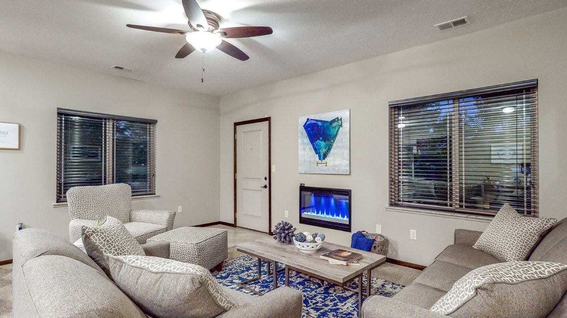 The spacious living area in the Cedar features an electric fireplace