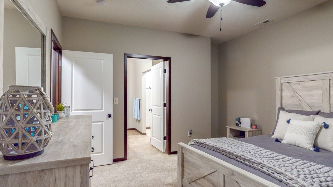 The master bedroom features an attached bathroom and spacious closet in the Cedar floor plan