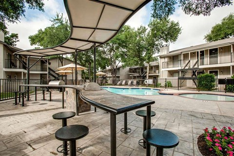 Courtyards of Roses Apartments pool area with shaded seating
