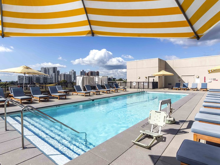 Pool sun deck with teak lounge chairs and yellow striped umbrellas and Stamford skyline in background