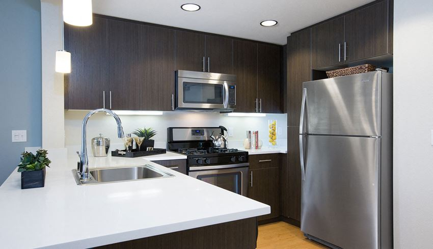 Modern kitchen with stainless steel appliances and white counter tops