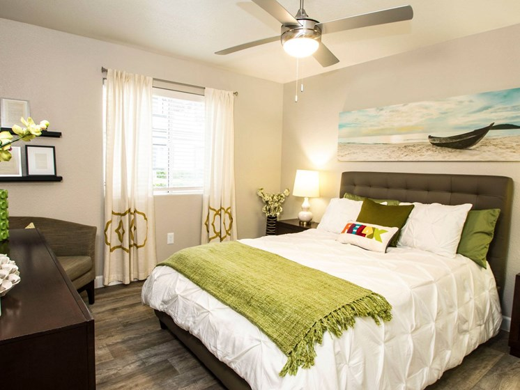 Master bedrooms with large window and ceiling fan