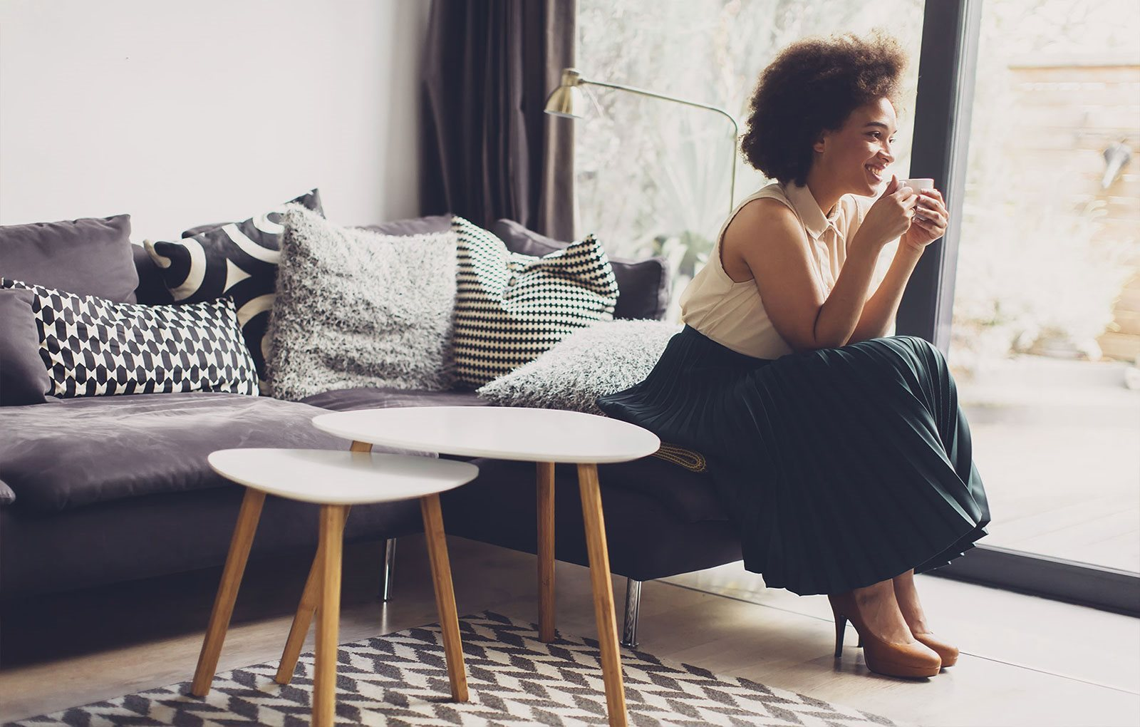 stock image- woman drinking coffee in living room