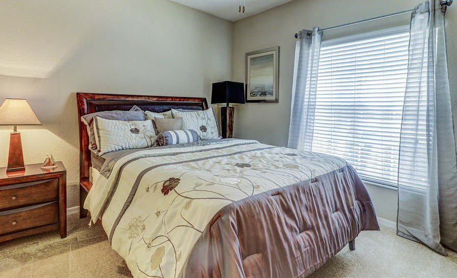 Bedroom With Expansive Windows at Plantation Gardens Apartments, Florida