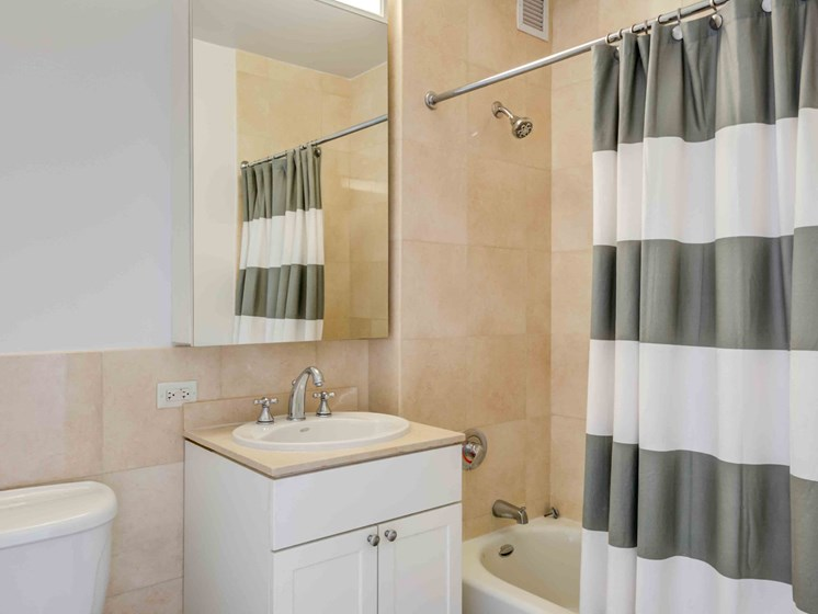 Model apartment bathroom with vanity and tub shower