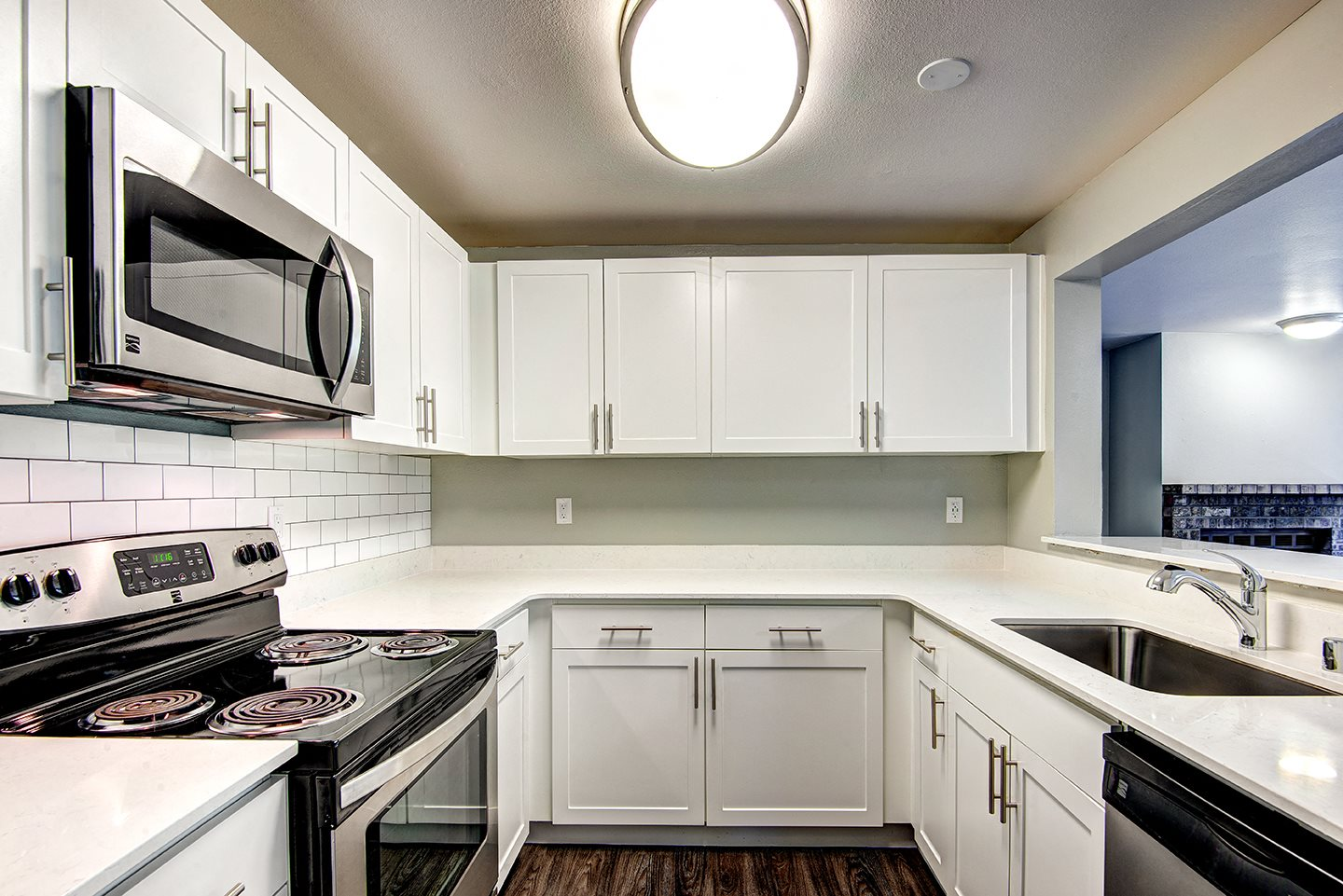 renovated unit kitchen featuring white cabinets,