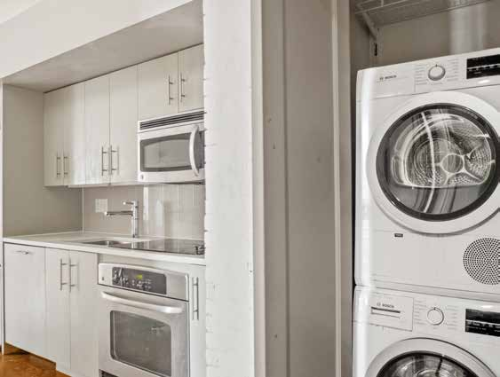 kitchen with white cabinets and laundry machines