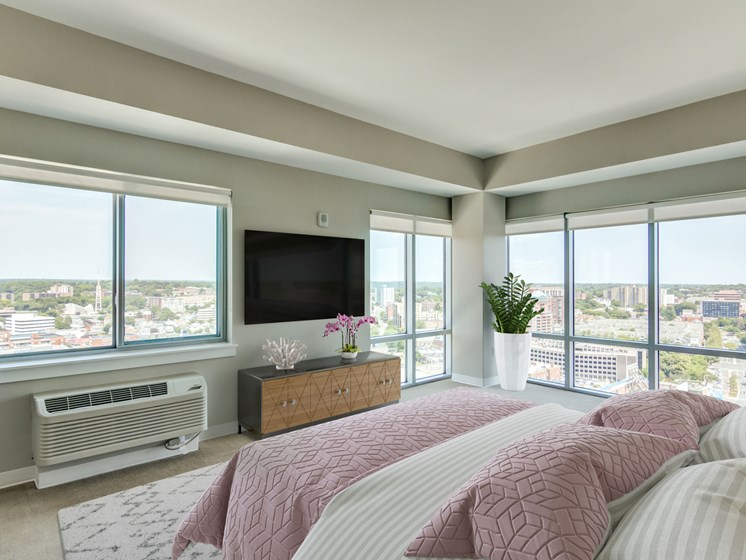 master bedroom with large windows that offer views of the city
