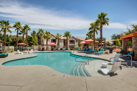 Apartments in Henderson, NV - Tesoro Ranch Swimming Pool Surrounded by Palm Trees and Lounge Chair Seating