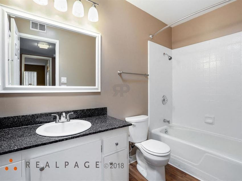 Fremont CA Apartments-Logan Park Apartments Bathroom With Large Tub With Square Tile And Dark Granite Sinktop
