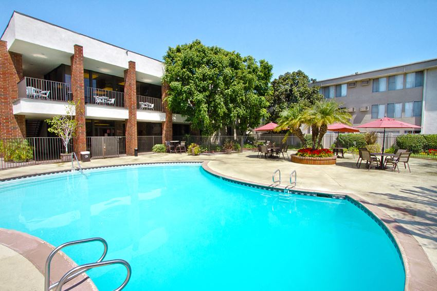 Apartments for Rent in Downey - Park Regency Club Swimming Pool Enclosed in Gated Area With Poolside Seating and Tables