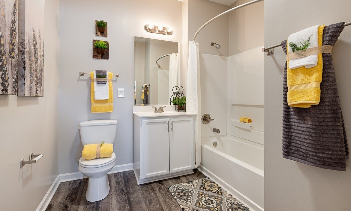 Spacious bathroom with vinyl flooring, white storage cabinets and soaking tub at The Summit on 401.