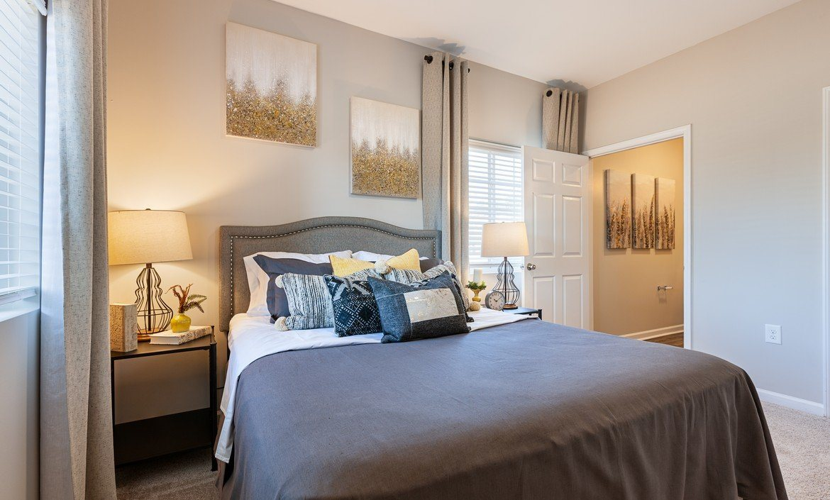 Spacious bedroom with natural lighting and plush carpeting at The Summit on 401