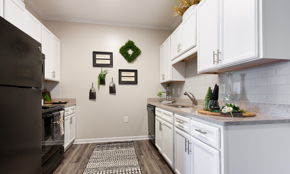 Spacious kitchen with white cabinetry and black energy efficient appliances at The Summit on 401 in Fayetteville, NC