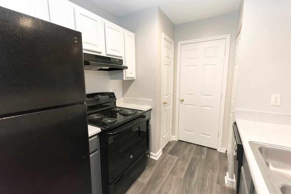 Renovated kitchen with black energy efficient appliances at The Avalon apartment homes in Charlotte, NC