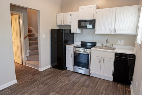 Spacious kitchen with white cabinetry,  black energy efficient appliances and plank style flooring