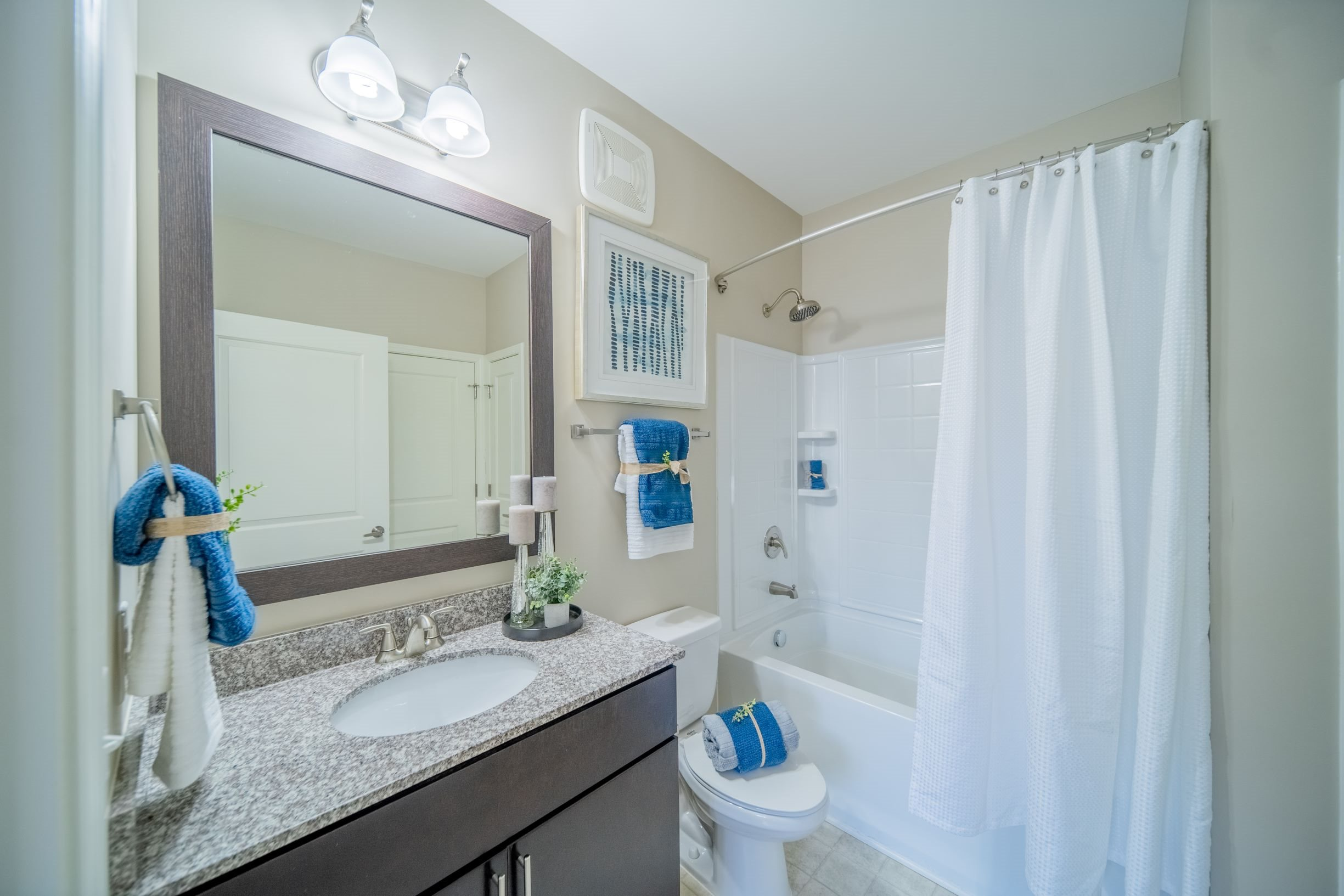 Spacious bathroom with granite countertops, framed mirror, and soaking tub at Piedmont Place in Greensboro, NC